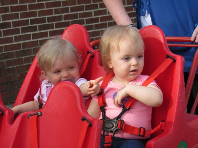 babies taking a ride on red cart